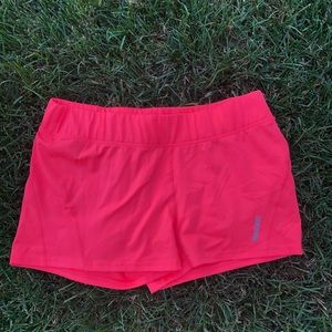 Reebok play dry shorts in a coral color